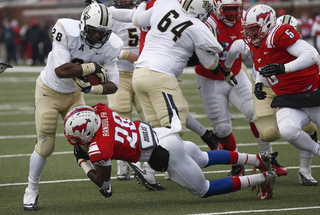 Dec 7, 2013; Dallas, TX, USA; UCF Knights running back William Stanback (28) runs with the ball as Southern Methodist Mustangs defensive back Shakiel Randolph (28) tackles during the second half of an NCAA football game at Gerald J. Ford Stadium. UCF Knights won 17-13. Mandatory Credit: Jim Cowsert-USA TODAY Sports