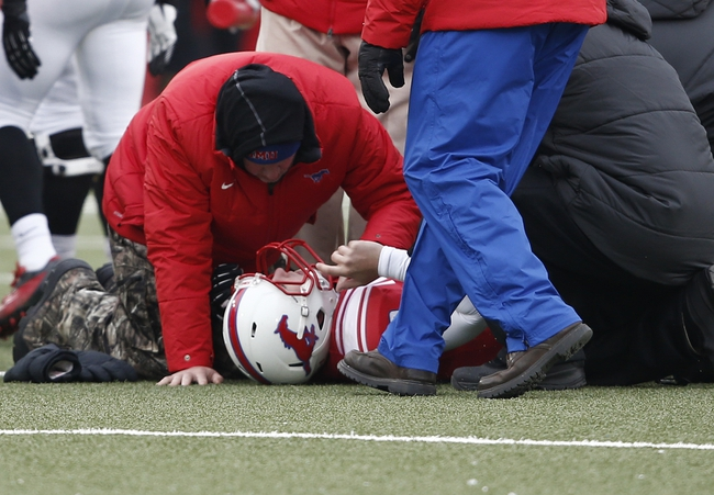 Dec 7, 2013; Dallas, TX, USA; Southern Methodist Mustangs quarterback Neal Burcham (12) is injured against the UCF Knights during the second half of an NCAA football game at Gerald J. Ford Stadium. UCF Knights won 17-13. Mandatory Credit: Jim Cowsert-USA TODAY Sports
