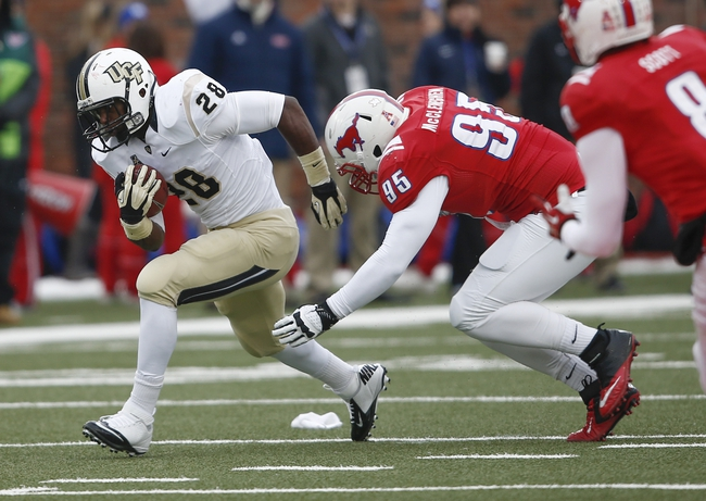 Dec 7, 2013; Dallas, TX, USA; UCF Knights running back William Stanback (28) runs with the ball against Southern Methodist Mustangs defensive lineman Andrew McCleneghen (95) during the second half of an NCAA football game at Gerald J. Ford Stadium. UCF Knights won 17-13. Mandatory Credit: Jim Cowsert-USA TODAY Sports