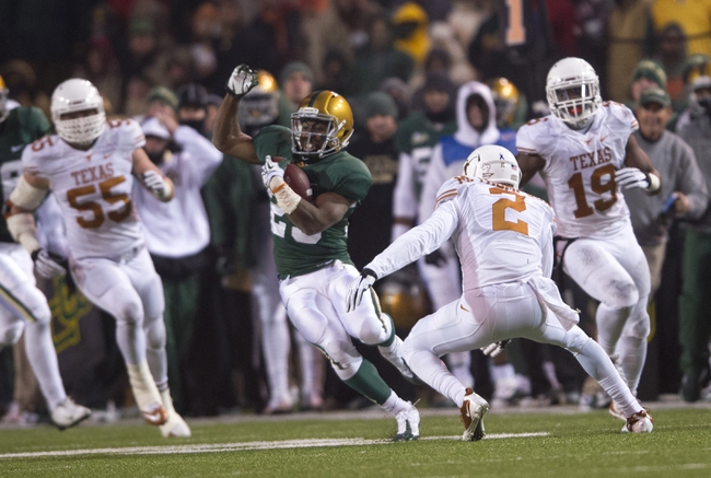 Dec 7, 2013; Waco, TX, USA; Baylor Bears running back Lache Seastrunk (25) carries the ball as Texas Longhorns safety Mykkele Thompson (2) chases during the second half at Floyd Casey Stadium. The Bears won 30-10 to win the Big 12 championship. Mandatory Credit: Jerome Miron-USA TODAY Sports