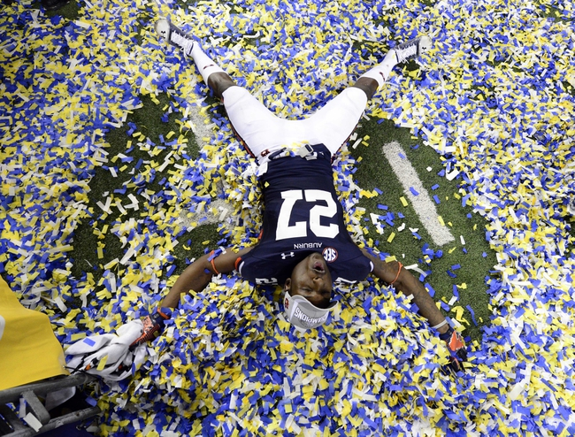 Dec 7, 2013; Atlanta, GA, USA; Auburn Tigers defensive back Robenson Therezie (27) plays in confetti after defeating the Missouri Tigers in the 2013 SEC Championship game at Georgia Dome. Auburn won 59-42. Mandatory Credit: John David Mercer-USA TODAY Sports