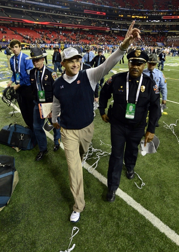Dec 7, 2013; Atlanta, GA, USA; Auburn Tigers head coach Gus Malzahn salutes the fans as he walks off the field after defeating the Missouri Tigers in the 2013 SEC Championship game at Georgia Dome. Auburn won 59-42. Mandatory Credit: John David Mercer-USA TODAY Sports