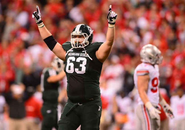 Dec 7, 2013; Indianapolis, IN, USA; Michigan State Spartans center Travis Jackson (63) celebrates after a scored touchdown during the fourth quarter of the 2013 Big 10 Championship game against the Ohio State Buckeyes at Lucas Oil Stadium. Mandatory Credit: Andrew Weber-USA TODAY Sports