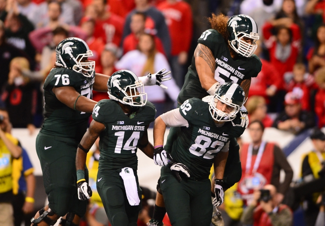 Dec 7, 2013; Indianapolis, IN, USA; Michigan State Spartans tight end Josiah Price (82) celebrates with teammates after catching a pass for a touchdown during the third quarter of the 2013 Big 10 Championship game against the Ohio State Buckeyes  at Lucas Oil Stadium. Mandatory Credit: Andrew Weber-USA TODAY Sports