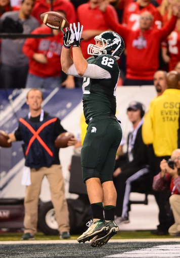 Dec 7, 2013; Indianapolis, IN, USA; Michigan State Spartans tight end Josiah Price (82) catches a pass in the end zone for a touchdown during the fourth quarter of the 2013 Big 10 Championship game against the Ohio State Buckeyes at Lucas Oil Stadium. Mandatory Credit: Andrew Weber-USA TODAY Sports