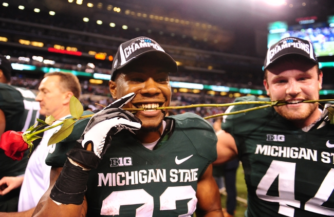 Dec 7, 2013; Indianapolis, IN, USA; Michigan State Spartans running back Jeremy Langford (33) with roses after defeating Ohio State Buckeyes 34-24 to win the 2013 Big 10 Championship game  at Lucas Oil Stadium. Mandatory Credit: Andrew Weber-USA TODAY Sports