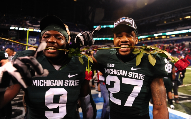 Dec 7, 2013; Indianapolis, IN, USA; Michigan State Spartans safety Isaiah Lewis (9) and safety Kurtis Drummond (27) with roses after defeating Ohio State Buckeyes 34-24 to win the 2013 Big 10 Championship game  at Lucas Oil Stadium. Mandatory Credit: Andrew Weber-USA TODAY Sports