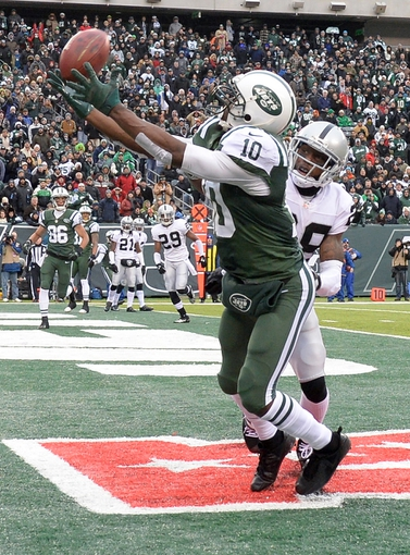 Dec 8, 2013; East Rutherford, NJ, USA; New York Jets wide receiver Santonio Holmes (10) is unable to catch a pass in the end zone against Oakland Raiders cornerback Phillip Adams (28) in the first half during the game at MetLife Stadium. Mandatory Credit: Robert Deutsch-USA TODAY Sports
