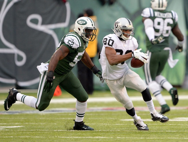 Dec 8, 2013; East Rutherford, NJ, USA; Oakland Raiders wide receiver Rod Streater (80) runs away from New York Jets inside linebacker David Harris (52)  during the game at MetLife Stadium. Mandatory Credit: Robert Deutsch-USA TODAY Sports