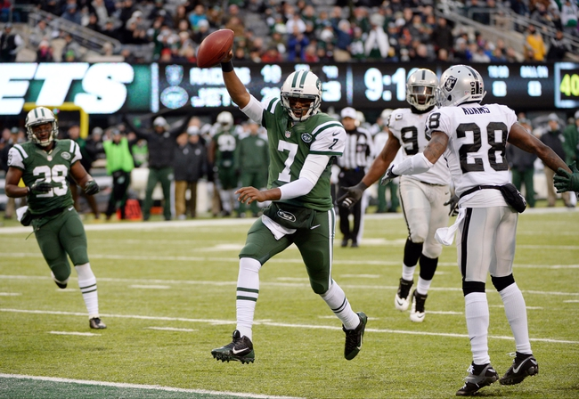 Dec 8, 2013; East Rutherford, NJ, USA; New York Jets quarterback Geno Smith (7) scores a touchdown in the second half against the Oakland Raiders during the game at MetLife Stadium. Mandatory Credit: Robert Deutsch-USA TODAY Sports