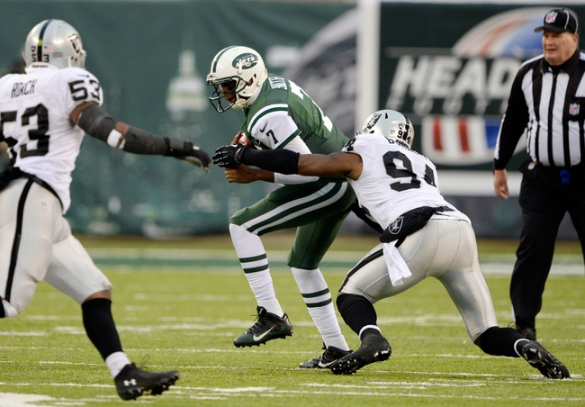 Dec 8, 2013; East Rutherford, NJ, USA; New York Jets quarterback Geno Smith (7) is sacked by Oakland Raiders outside linebacker Kevin Burnett (94) during the game at MetLife Stadium. Mandatory Credit: Robert Deutsch-USA TODAY Sports