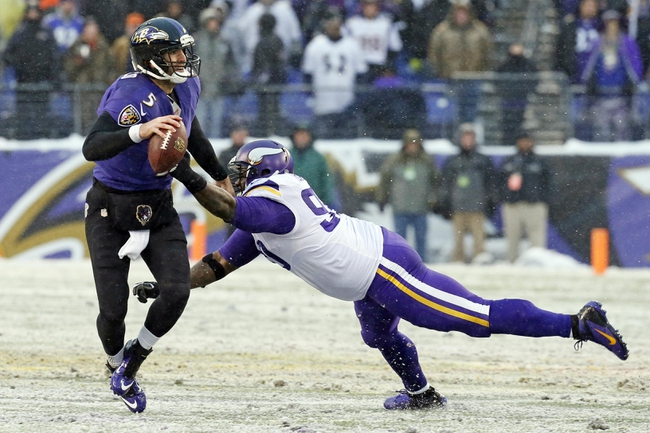 Dec 8, 2013; Baltimore, MD, USA; Baltimore Ravens quarterback Joe Flacco (5) looks to pass under pressure from Minnesota Vikings tackle Fred Evans (90) at M&T Bank Stadium. Mandatory Credit: Mitch Stringer-USA TODAY Sports