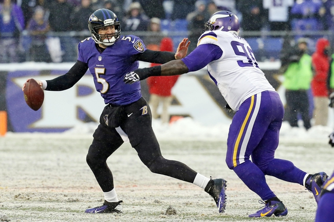 Dec 8, 2013; Baltimore, MD, USA; Baltimore Ravens quarterback Joe Flacco (5) looks to pass under pressure from Minnesota Vikings tackle Fred Evans (90) at M&T Bank Stadium. Mandatory Credit: Mitch Stringer-USA TODAY