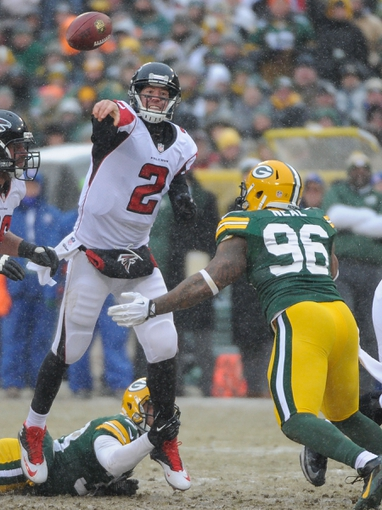 Dec 8, 2013; Green Bay, WI, USA;  Atlanta Falcons quarterback Matt Ryan (2) gets a pass away while under pressure from Green Bay Packers defensive end Mike Neal (96) and cornerback Micah Hyde (33) in the 4th quarter at Lambeau Field. Mandatory Credit: Benny Sieu-USA TODAY Sports
