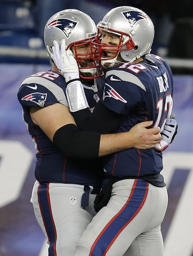 Dec 8, 2013; Foxborough, MA, USA; New England Patriots quarterback Tom Brady (12) reacts with center Ryan Wendell (62) after a touchdown in the last seconds of play against the Cleveland Browns in the second half at Gillette Stadium. The Patriots defeated the Cleveland Browns 27-26. Mandatory Credit: David Butler II-USA TODAY Sports