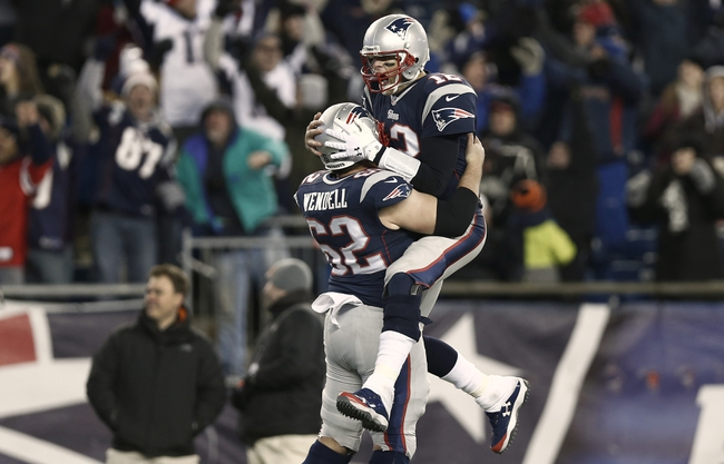 Dec 8, 2013; Foxborough, MA, USA; New England Patriots quarterback Tom Brady (12) leaps into the arms of center Ryan Wendell (62) after he threw the winning touchdown pass during the fourth quarter of New England's 27-26 win over the Cleveland Browns at Gillette Stadium. Mandatory Credit: Winslow Townson-USA TODAY Sports