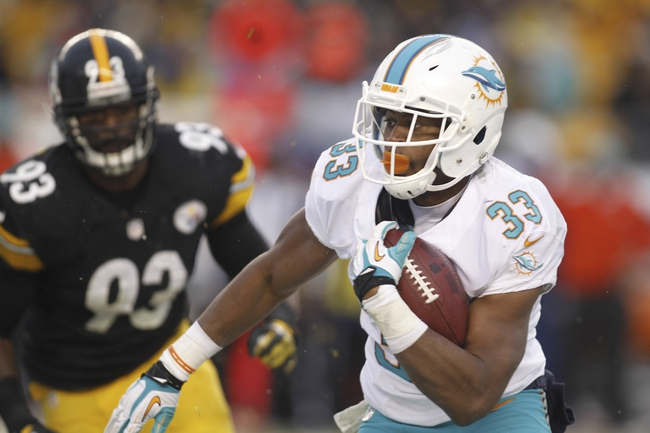 Dec 8, 2013; Pittsburgh, PA, USA; Miami Dolphins running back Daniel Thomas (33) rushes the ball against the Pittsburgh Steelers during the fourth quarter at Heinz Field. The Miami Dolphins won 34-28. Mandatory Credit: Charles LeClaire-USA TODAY Sports