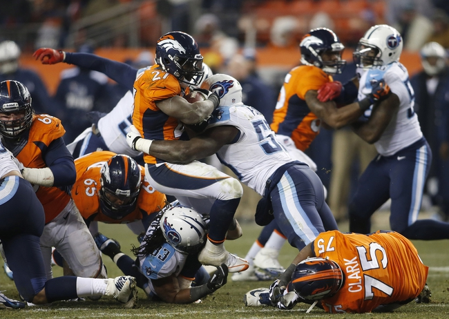 Dec 8, 2013; Denver, CO, USA; Denver Broncos running back Knowshon Moreno (27) is tackled by Tennessee Titans linebacker Moise Fokou (53) during the second half at Sports Authority Field at Mile High. The Broncos won 51-28.  Mandatory Credit: Chris Humphreys-USA TODAY Sports