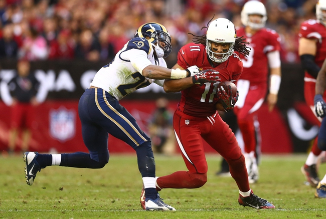 Dec 8, 2013; Phoenix, AZ, USA; Arizona Cardinals wide receiver Larry Fitzgerald (11) controls the ball under pressure from St. Louis Rams safety T.J. McDonald in the second half at University of Phoenix Stadium. The Cardinals defeated the Rams 30-10. Mandatory Credit: Mark J. Rebilas-USA TODAY Sports