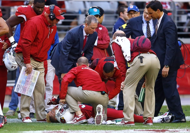 Dec 8, 2013; Phoenix, AZ, USA; Arizona Cardinals head coach Bruce Arians (left) looks on as trainers tend to Tyrann Mathieu after suffering an injury in the third quarter against the St. Louis Rams at University of Phoenix Stadium. The Cardinals defeated the Rams 30-10. Mandatory Credit: Mark J. Rebilas-USA TODAY Sports
