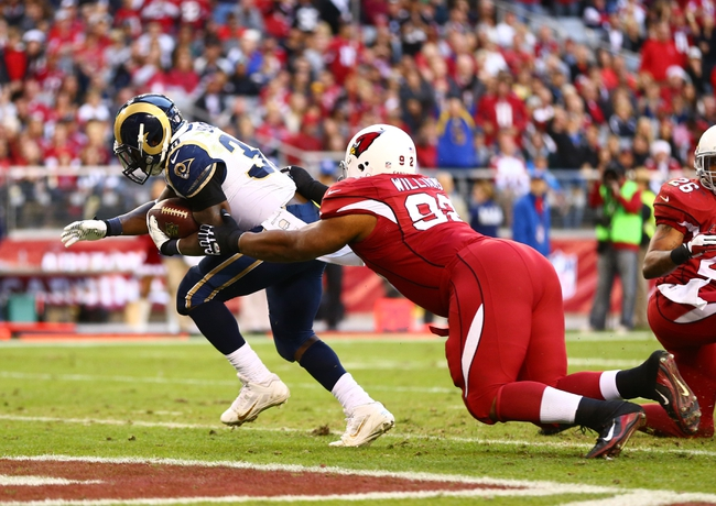 Dec 8, 2013; Phoenix, AZ, USA; St. Louis Rams running back Zac Stacy (30) scores a touchdown in the fourth quarter under pressure from Arizona Cardinals defensive tackle Dan Williams at University of Phoenix Stadium. The Cardinals defeated the Rams 30-10. Mandatory Credit: Mark J. Rebilas-USA TODAY Sports