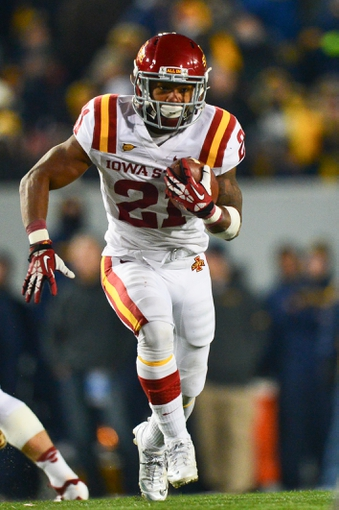 Nov 30, 2013; Morgantown, WV, USA;  Iowa State Cyclones running back Shontrelle Johnson (21) runs with the ball in the fourth quarter of the game against West Virginia Mountaineers at Milan Puskar Stadium. The Iowa State Cyclones defeated West Virginia Mountaineers 52-44 in the third overtime. Mandatory Credit: Tommy Gilligan-USA TODAY Sports
