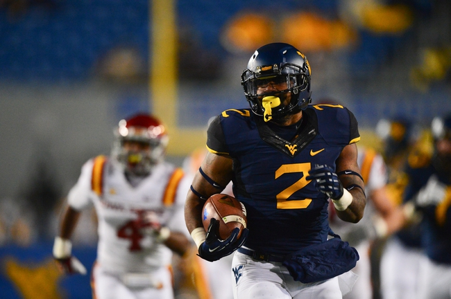 Nov 30, 2013; Morgantown, WV, USA; West Virginia Mountaineers running back Dreamius Smith (2) runs with the ball during the third quarter of the game against Iowa State Cyclones at Milan Puskar Stadium. The Iowa State Cyclones defeated West Virginia Mountaineers 52-44 in the third overtime. Mandatory Credit: Tommy Gilligan-USA TODAY Sports