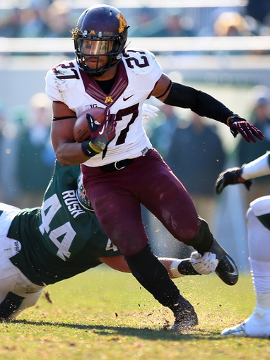 Nov 30, 2013; East Lansing, MI, USA; Minnesota Golden Gophers running back David Cobb (27) is tripped up by Michigan State Spartans defensive end Marcus Rush (44 during the 2nd half a game at Spartan Stadium. MSU won 14-3.  Mandatory Credit: Mike Carter-USA TODAY Sports