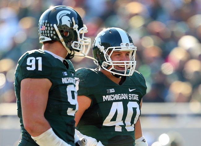 Nov 30, 2013; East Lansing, MI, USA; Michigan State Spartans linebacker Max Bullough (40) and Michigan State Spartans defensive tackle Tyler Hoover (91) talk on field during the 2nd half a game at Spartan Stadium. MSU won 14-3.  Mandatory Credit: Mike Carter-USA TODAY Sports