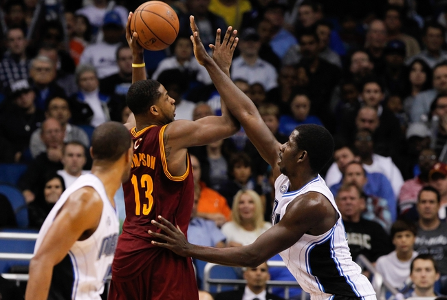 Dec 13, 2013; Orlando, FL, USA; Cleveland Cavaliers power forward Tristan Thompson (13) shoots over Orlando Magic point guard E'Twaun Moore (55) during the second half at Amway Center. Cleveland Cavaliers defeated the Orlando Magic 109-100. Mandatory Credit: Kim Klement-USA TODAY Sports