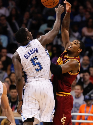 Dec 13, 2013; Orlando, FL, USA; Cleveland Cavaliers point guard Kyrie Irving (2) and Orlando Magic shooting guard Victor Oladipo (5) go after the ball during the second half at Amway Center. Cleveland Cavaliers defeated the Orlando Magic 109-100. Mandatory Credit: Kim Klement-USA TODAY Sports