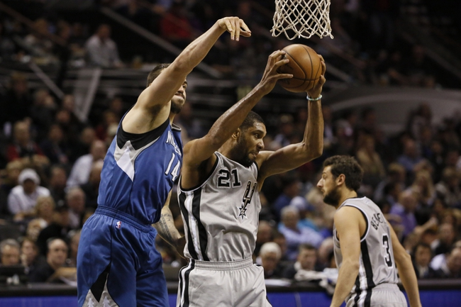 Dec 13, 2013; San Antonio, TX, USA; San Antonio Spurs forward Tim Duncan (21) pulls down a rebound over Minnesota Timberwolves center Nikola Pekovic (14) during the second half at AT&T Center. The Spurs won 117-110. Mandatory Credit: Soobum Im-USA TODAY Sports