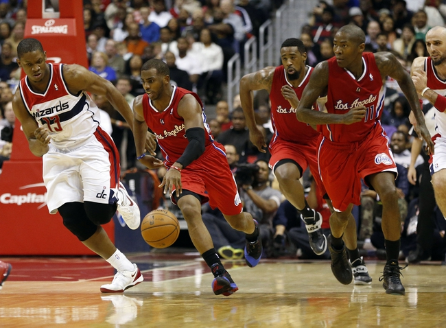 Dec 14, 2013; Washington, DC, USA; Los Angeles Clippers point guard Chris Paul (3) dribbles the ball past Washington Wizards center Kevin Seraphin (13) in the third quarter at Verizon Center. The Clippers won 113-97. Mandatory Credit: Geoff Burke-USA TODAY Sports