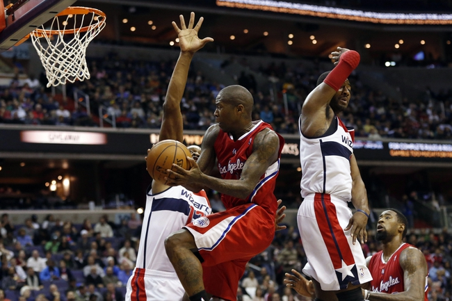 Dec 14, 2013; Washington, DC, USA; Los Angeles Clippers shooting guard Jamal Crawford (11) prepares to shoot the ball as Washington Wizards center Kevin Seraphin (13) and Wizards point guard John Wall (2) defend in the third quarter at Verizon Center. The Clippers won 113-97. Mandatory Credit: Geoff Burke-USA TODAY Sports