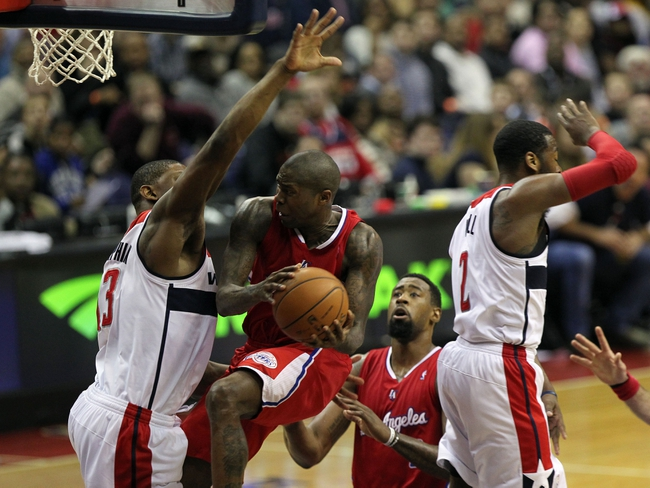 Dec 14, 2013; Washington, DC, USA; Los Angeles Clippers shooting guard Jamal Crawford (11) shoots the ball as Washington Wizards center Kevin Seraphin (13) defends in the third quarter at Verizon Center. Mandatory Credit: Geoff Burke-USA TODAY Sports