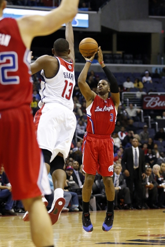 Dec 14, 2013; Washington, DC, USA; Los Angeles Clippers point guard Chris Paul (3) shoots the ball as Washington Wizards center Kevin Seraphin (13) defends in the fourth quarter at Verizon Center. Mandatory Credit: Geoff Burke-USA TODAY Sports