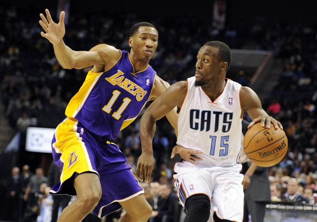 Dec 14, 2013; Charlotte, NC, USA; Charlotte Bobcats guard Kemba Walker (15) drives past Los Angeles Lakers guard forward Wesley Johnson (11) during the second half of the game at Time Warner Cable Arena. Lakers win 88-85. Mandatory Credit: Sam Sharpe-USA TODAY Sports