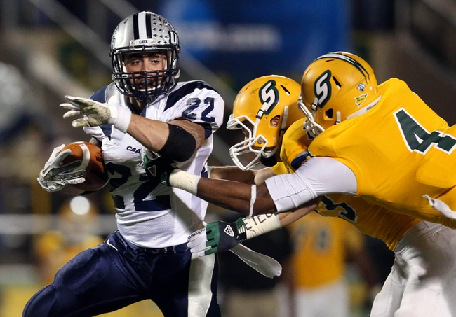 Dec 14, 2013; Hammond, LA, USA; New Hampshire Wildcats running back Nico Steriti (22) fights off Southeastern Louisiana Lions defensive back Tyler Stoddard (23) and defensive back Theo Alexander (4) in the second half at Strawberry Stadium. New Hampshire defeated Southeastern Louisiana 20-17. Mandatory Credit: Crystal LoGiudice-USA TODAY Sports