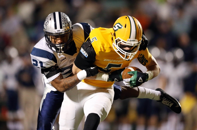 Dec 14, 2013; Hammond, LA, USA; New Hampshire Wildcats cornerback Steven Thames (21) tackles Southeastern Louisiana Lions wide receiver Chris Malott (5) in the second half at Strawberry Stadium. New Hampshire defeated Southeastern Louisiana 20-17. Mandatory Credit: Crystal LoGiudice-USA TODAY Sports