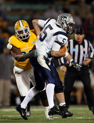 Dec 14, 2013; Hammond, LA, USA; New Hampshire Wildcats quarterback Sean Goldrich (5) fights off Southeastern Louisiana Lions defensive lineman Marquel Combs (90) in the second half at Strawberry Stadium. New Hampshire defeated Southeastern Louisiana 20-17. Mandatory Credit: Crystal LoGiudice-USA TODAY Sports
