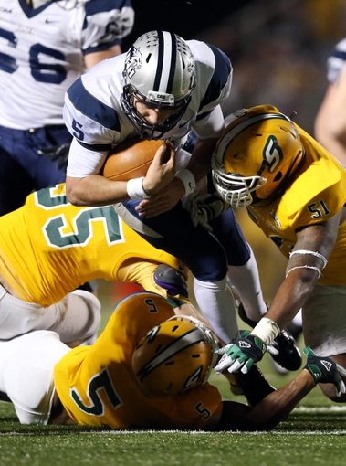 Dec 14, 2013; Hammond, LA, USA; New Hampshire Wildcats quarterback Sean Goldrich (5) is tackled by Southeastern Louisiana Lions linebacker Justin Church (95) and defensive back John Graves (5) and linebacker Cqulin Hubert (51) in the second half at Strawberry Stadium. New Hampshire defeated Southeastern Louisiana 20-17. Mandatory Credit: Crystal LoGiudice-USA TODAY Sports
