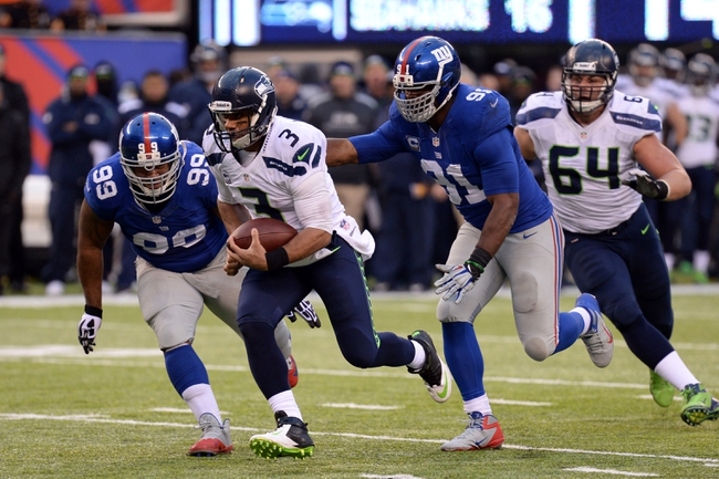 Dec 15, 2013; East Rutherford, NJ, USA; Seattle Seahawks quarterback Russell Wilson (3) runs by New York Giants defensive tackle Cullen Jenkins (99) and defensive end Justin Tuck (91) during the second half at MetLife Stadium. Mandatory Credit: Joe Camporeale-USA TODAY Sports