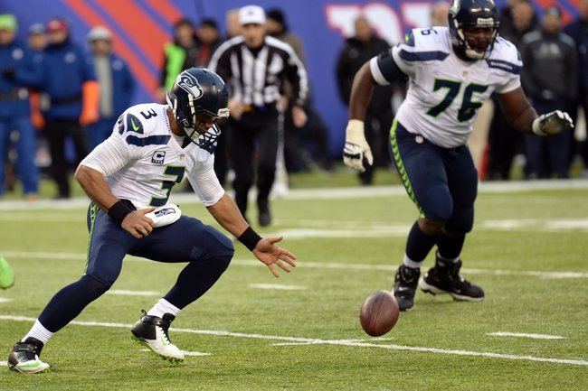 Dec 15, 2013; East Rutherford, NJ, USA;Seattle Seahawks quarterback Russell Wilson (3) recovers his own fumble against the New York Giants during the second half at MetLife Stadium. Mandatory Credit: Joe Camporeale-USA TODAY Sports