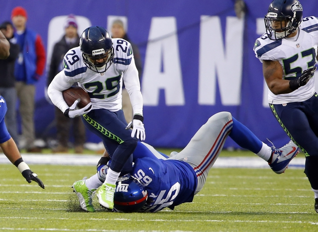 Dec 15, 2013; East Rutherford, NJ, USA;  New York Giants tackle Will Beatty (65) tackles Seattle Seahawks free safety Earl Thomas (29) after an interception during the game at MetLife Stadium. Seattle Seahawks defeat the New York Giants 23-0. Mandatory Credit: Jim O'Connor-USA TODAY Sports