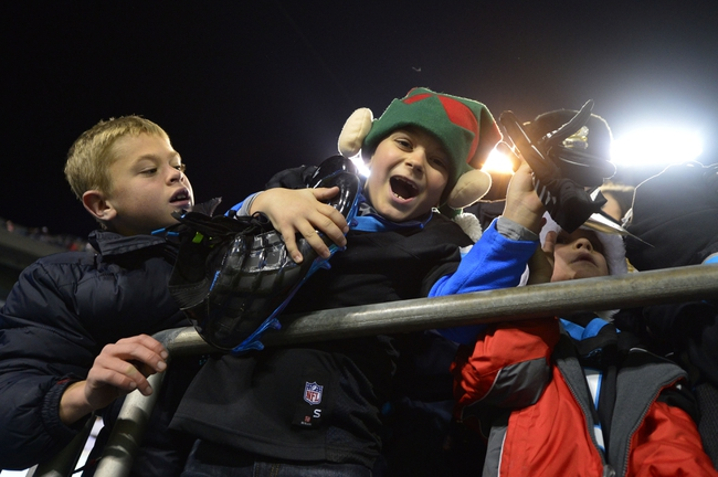 Dec 15, 2013; Charlotte, NC, USA; Seven year old Carolina Panthers fan Trip Simmons reacts after receiving wide receiver Steve Smith (89) shoes after the game. The Panthers defeated the Jets 30-20 at Bank of America Stadium. Mandatory Credit: Bob Donnan-USA TODAY Sports