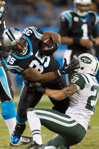Dec 15, 2013; Charlotte, NC, USA; Carolina Panthers fullback Mike Tolbert (35) runs over New York Jets cornerback Dee Milliner (27) during the third quarter at Bank of America Stadium. Panthers defeated the Jets 30-20. Mandatory Credit: Jeremy Brevard-USA TODAY Sports