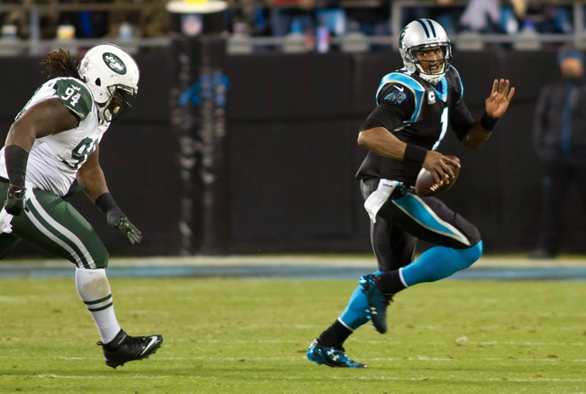 Dec 15, 2013; Charlotte, NC, USA; Carolina Panthers quarterback Cam Newton (1) runs the ball while being pursued by New York Jets nose tackle Damon Harrison (94) at Bank of America Stadium. Panthers defeated the Jets 30-20. Mandatory Credit: Jeremy Brevard-USA TODAY Sports
