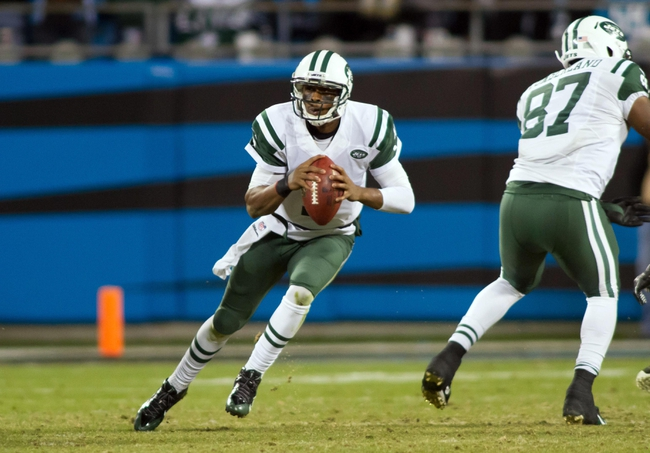 Dec 15, 2013; Charlotte, NC, USA; New York Jets quarterback Geno Smith (7) scrambles during the fourth quarter against the Carolina Panthers at Bank of America Stadium. Panthers defeated the Jets 30-20. Mandatory Credit: Jeremy Brevard-USA TODAY Sports