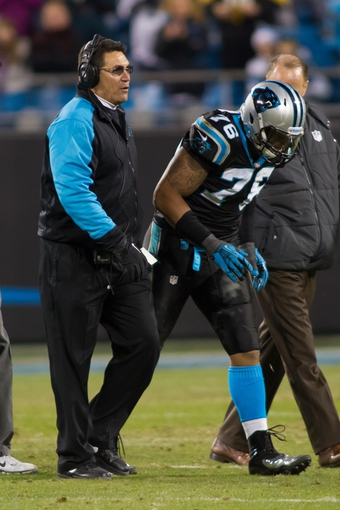 Dec 15, 2013; Charlotte, NC, USA; Carolina Panthers head coach Ron Rivera helps defensive end Greg Hardy (76) off the field after an injury during the fourth quarter at Bank of America Stadium. Panthers defeated the Jets 30-20. Mandatory Credit: Jeremy Brevard-USA TODAY Sports