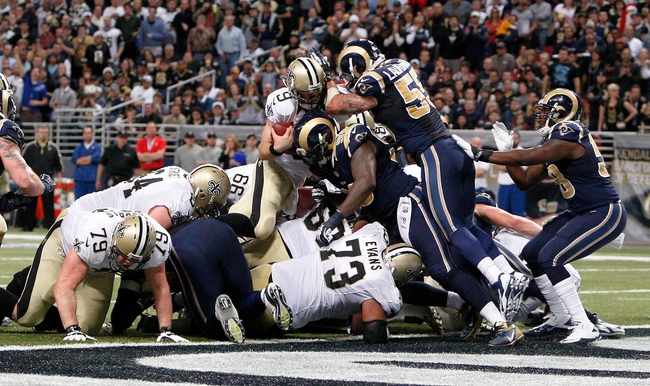 Dec 15, 2013; St. Louis, MO, USA;  New Orleans Saints quarterback Drew Brees (9) is stopped short of the end zone by St. Louis Rams middle linebacker James Laurinaitis (55) during the second half at the Edward Jones Dome. Mandatory Credit: Scott Kane-USA TODAY Sports